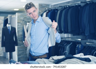 Man purchaser choosing waistcoat in the modern dress shop