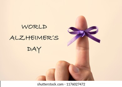 man with a purple ribbon tied to his forefinger and the text world alzheimers day on an off-white background