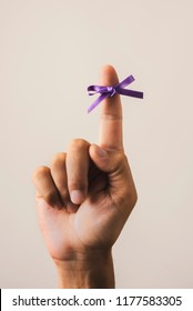 man with a purple ribbon tied to his forefinger, for the world alzheimers day, on an off-white background