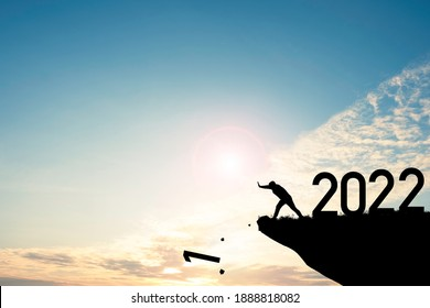 Man push number one down the cliff where has the number 2022 with blue sky and sunrise. It is symbol of starting and welcome happy new year 2022.