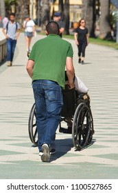 Man pushes disabled in wheeled chair