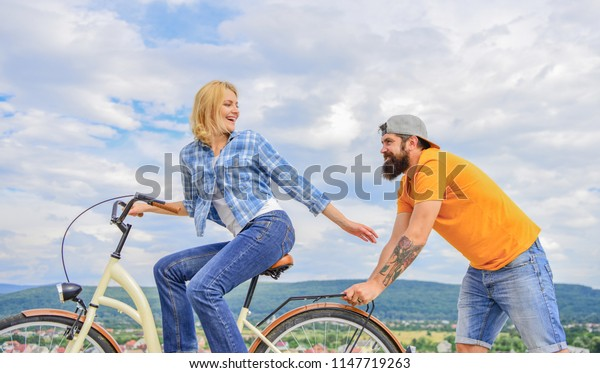 Man pushes girl ride bike. Girl cycling while man support her. Support helps believe in yourself. Feel impulse to start moving. Woman rides bicycle sky background. Push and promoting. Impulse to move.