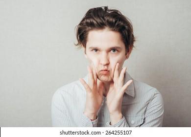 man pushes himself cheeks