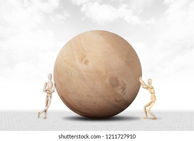 Man pushes a huge wooden ball and another sabotages it. Abstract image with a wooden puppet