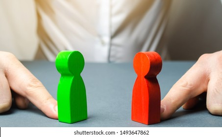 The man pushes the red and green figures to each other. The search for a compromise, mediation in negotiations. conflict of interest Analysis, situation. Reconciliation of the parties to the dispute