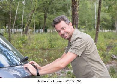 Man pushing a broken car down the road