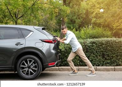 Man pushing broken car on road along city street