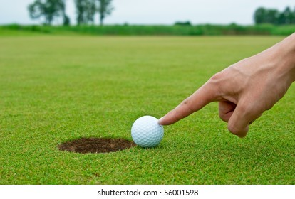 Man pushing golf ball into the hole