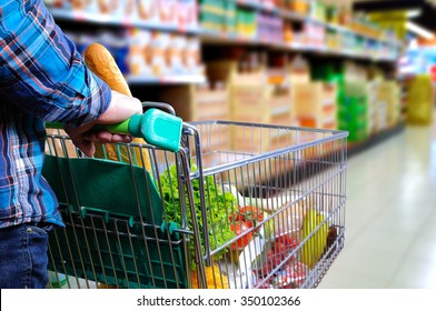 Man pushing shopping cart full of food in the supermarket aisle. Elevated rear view. horizontal composition