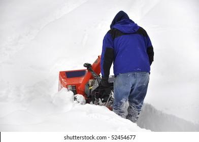 man pushing snow blower through deep snow