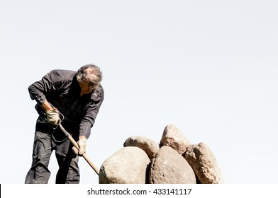 Man pushing  stones with pitchfork  on a white background, senior man puts stones in to a heap, tough human work, Labor, energy, human strength concept