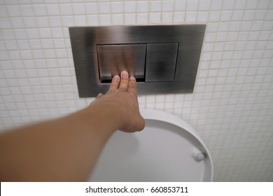 a man is pushing toilet flush button.