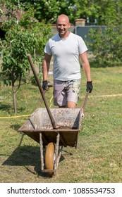 man pushing wheelbarrow. Young man pushing a wheelbarrow on the farm.