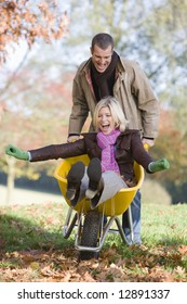 Man pushing wife through autumn leaves in wheelbarrow