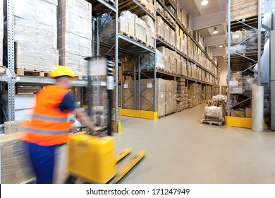 Man pushing a yellow forklift in huge store