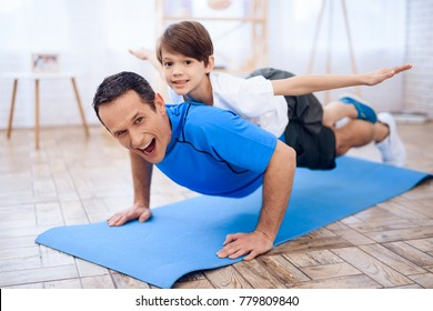 The man pushup from the floor with the boy on his back. This is father and son. They are at home.