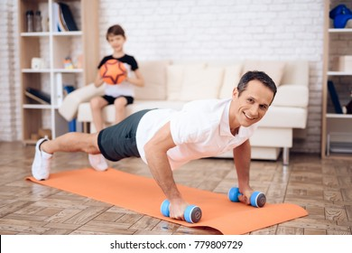 The man pushup, holding a dumbbell. Next to his son. They train together at home.