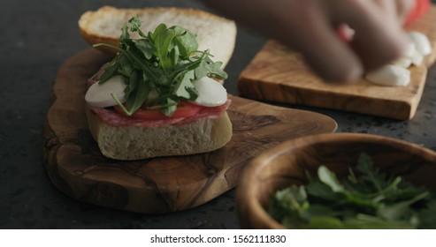 man put arugula on ciabatta slice on olive board