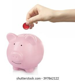 Man put coin into a piggy-bank