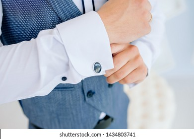 The man put on his shirt and straightens cufflinks. The groom fasten cufflinks on the cuffs of the shirt. The businessman fasten cufflinks on the cuffs of the shirt. Concept successful businessman.