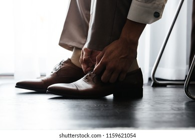 man put on leather brown shoes
