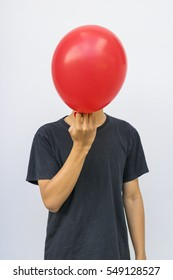 Man put the red balloon in front of his face like mask