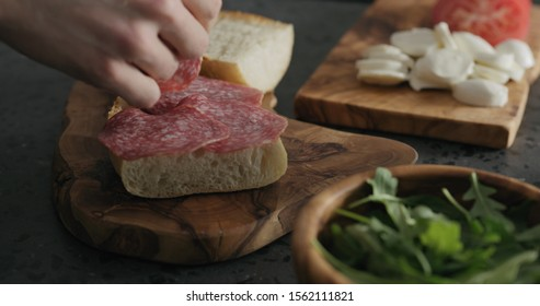 man put salami on ciabatta slice on olive board
