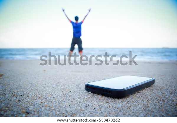 A man put smart phone on the beach sand and turn off it,stop connect to social network, concept of relax time.