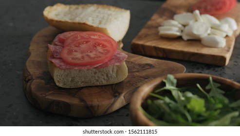 man put tomato on ciabatta slice on olive board