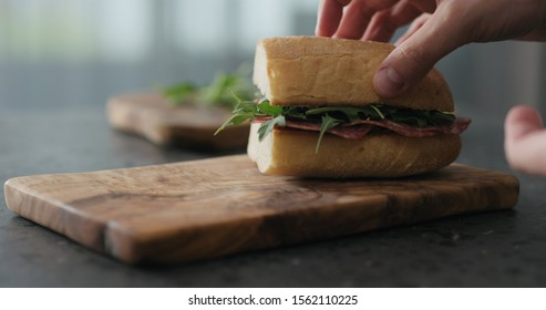 man put top on ciabatta sandwich with salami and cream cheese on olive board
