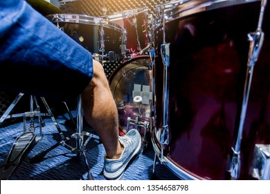 man put white sport shoes and playing the drum set and bass drum with foot in music room , the concept of musical instrument