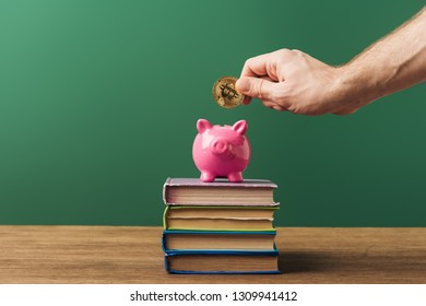 man puting coin in pink piggy bank on books with green background