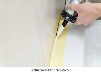 A man is puting the silicone sealant to caulk the joint between a washbasin and a wall.