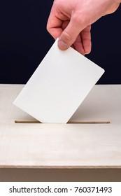 Man puts ballot in a voting box