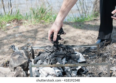man puts coal into the fire