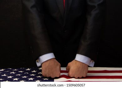 The man puts his fists on the table covered with the American flag. Concept: conflict, force, revenge and offense, threat
