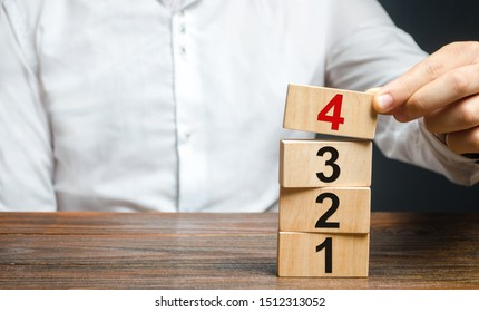 A man puts numbered wooden blocks on top of each other. Alternate items and conditions for implementation. Contract road map. Organization and systematization, step by step instructions.