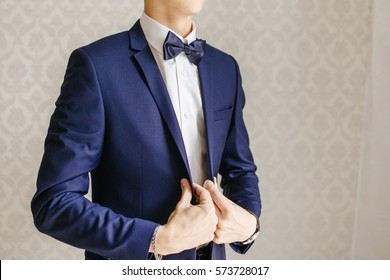 man puts on a blue jacket, blue jacket and bow tie on the man, businessman in a suit, morning groom, a man in a white shirt, blue suit and bow tie, wedding suit groom
