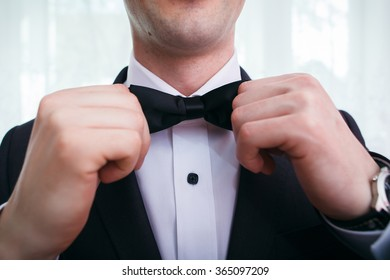 Man puts on bow tie
