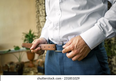 Man puts on brown belt. Focus on the buckle