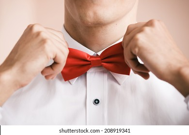 Man puts on red bow tie. Close up. Shallow depth of field. Focused on  bow tie.