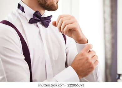 Man puts on shirt. Shallow depth of field. Focused on bow tie.