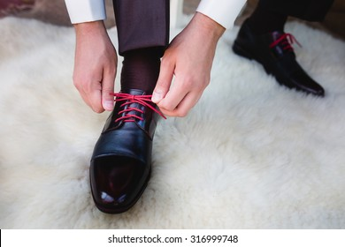 Man puts on shoes. Focus on the laces