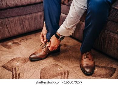 Man puts on stylish leather shoes