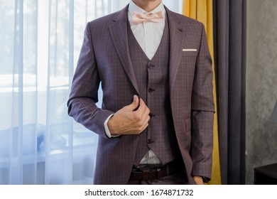 man puts on a suit and bow-tie