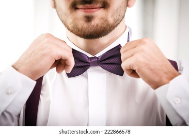Man puts on violet bow tie. Close up. Shallow depth of field. Focused on bow tie.