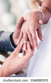 man puts on wedding ring on woman's finger