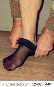A man puts on women's stockings. Concept of transvestite