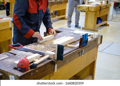 A man puts a piece of wood on a workbench for carpentry