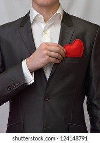 Man puts a red decorative heart in pocket